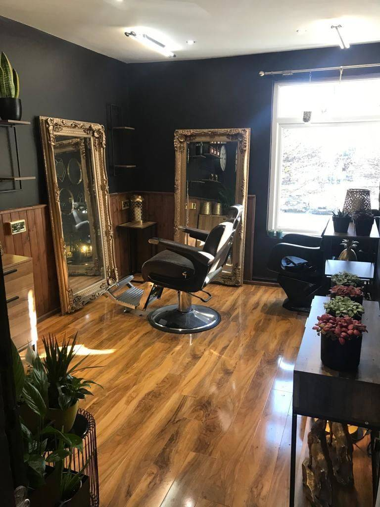 Photo of the inside of a barber shop, including a black barbers chair, two large mirrors, black painted walls, and a window.